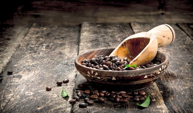 Grains de café dans un bol sur un fond en bois