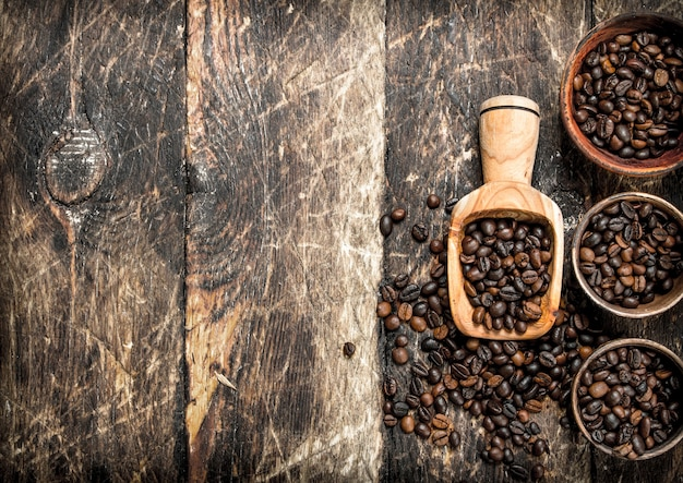 Grains de café dans des bols. sur un fond en bois.