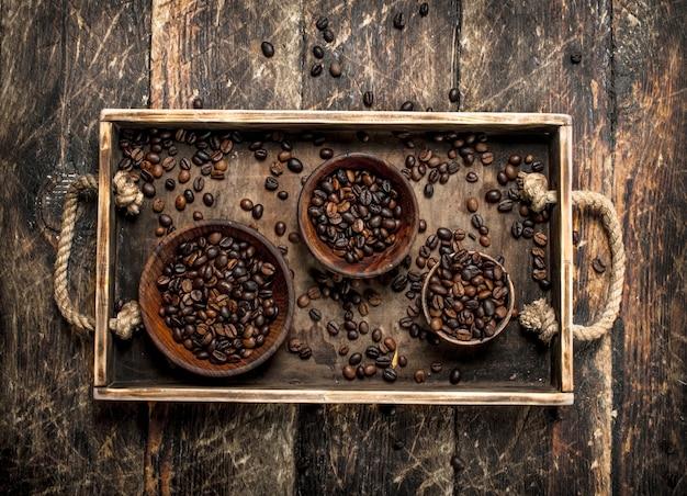Les grains de café dans des bols sur un plateau sur un fond en bois