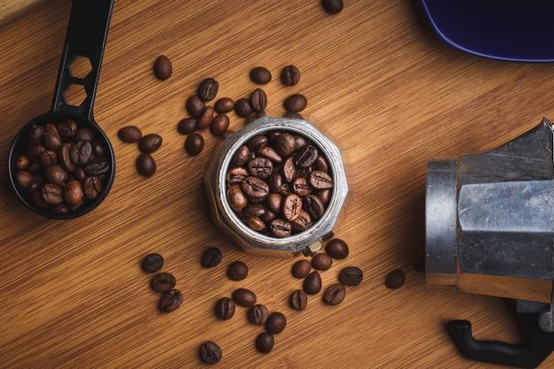 Grains de café dans une cafetière geyser sur une table en bois avec une tasse sur un plateau.