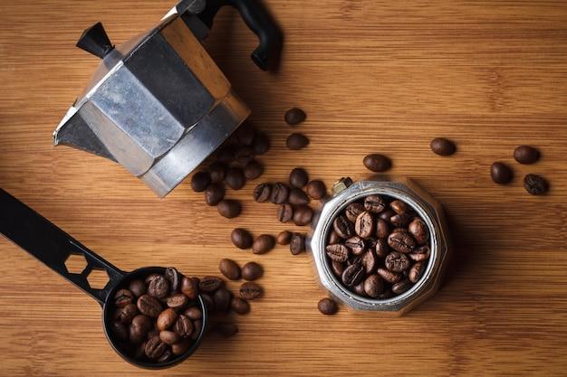 Grains de café dans une cafetière geyser sur une table en bois.