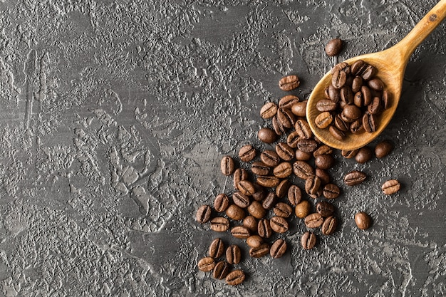 Grains de café dans une cuillère en bois sur fond de pierre