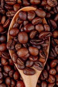 Grains de café dans une cuillère en bois sur les grains de café vue rapprochée