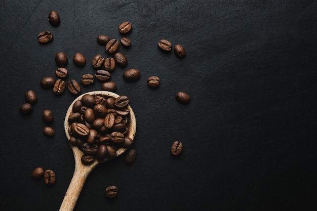 Grains de café dans une cuillère en bois sur une table sombre. vue de dessus.