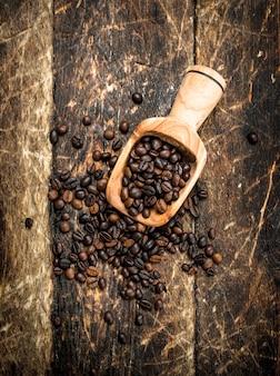 Grains de café dans une cuillère. sur un fond en bois.
