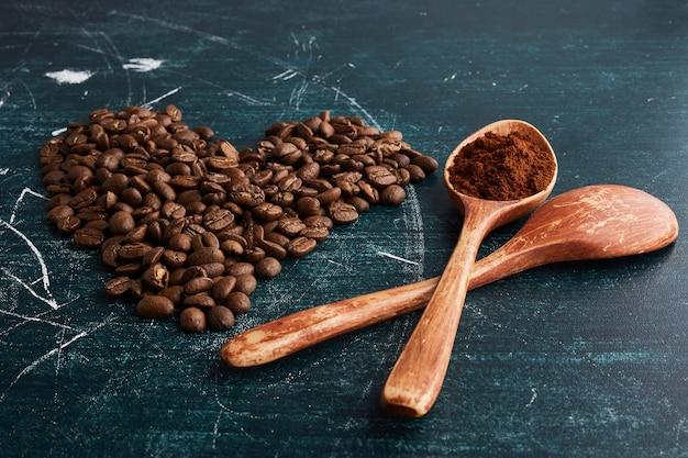 Grains de café dans des cuillères en bois et en forme de coeur.