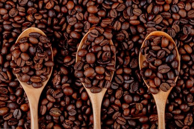 Grains de café dans des cuillères en bois sur la vue de dessus des grains de café