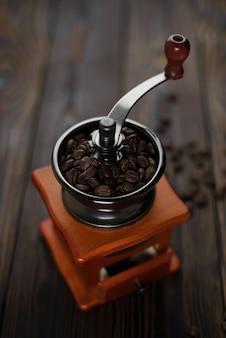 Grains de café dans un moulin à café manuel sur une table rustique sombre.