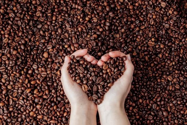 Grains de café dans les paumes de l'homme en forme de coeur sur fond de café