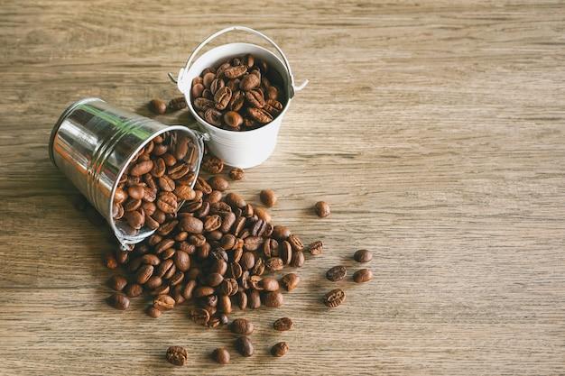Grains de café dans un petit seau d'eau en acier inoxydable sur fond de bois