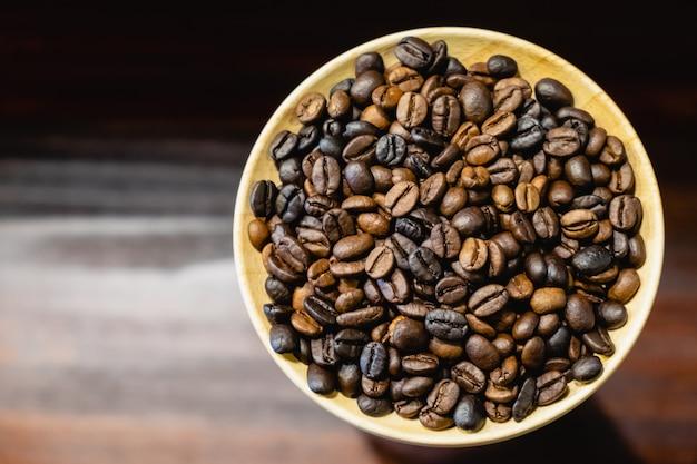 Les grains de café dans un plat en bois