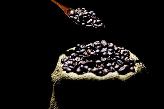 Grains de café dans un sac sur un fond de couleur sombre