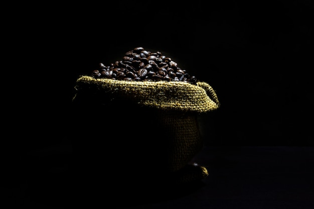 Grains de café dans un sac sur un fond sombre.