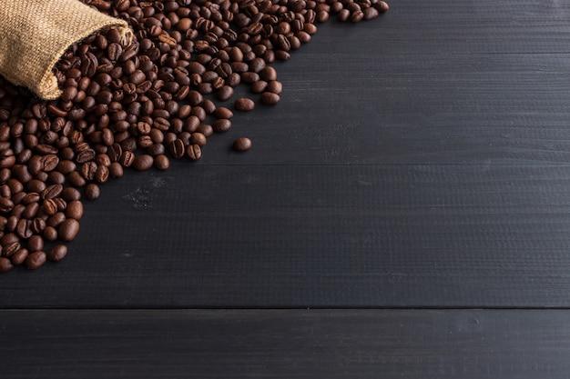 Grains de café dans un sac de jute sur vieux bois avec flou artistique et lumière en arrière-plan
