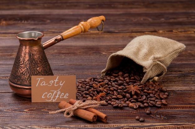 Grains de café dans un sac avec pot et tubes de cannelle sur bois