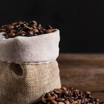 Grains de café dans un sac et sur la table