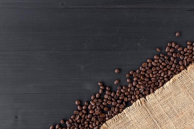 Grains de café dans un sac en toile de jute sur fond en bois ancien. vue de dessus
