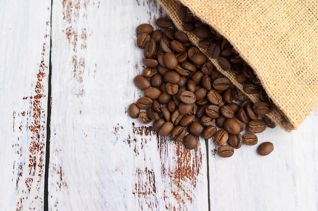 Grains de café dans des sacs de chanvre sur une table en bois blanc.