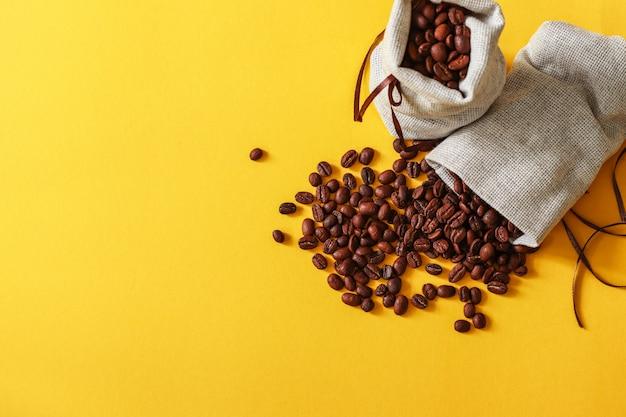 Grains de café dans des sacs sur fond jaune avec espace copie pour votre texte.