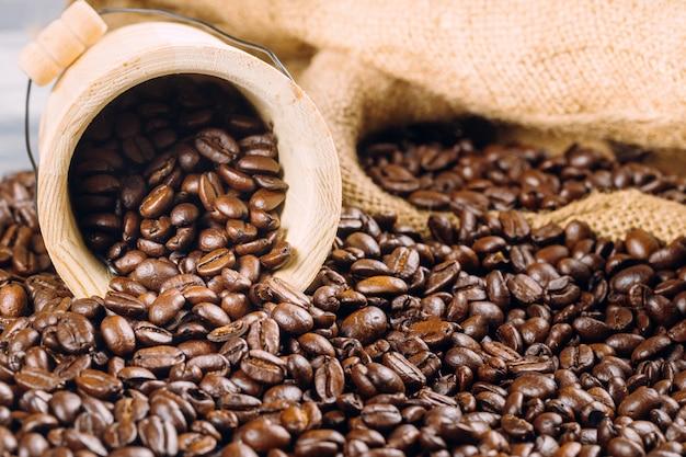Grains de café dans un seau décoratif sur des grains de café