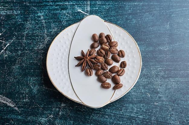 Grains de café dans une soucoupe en céramique blanche.