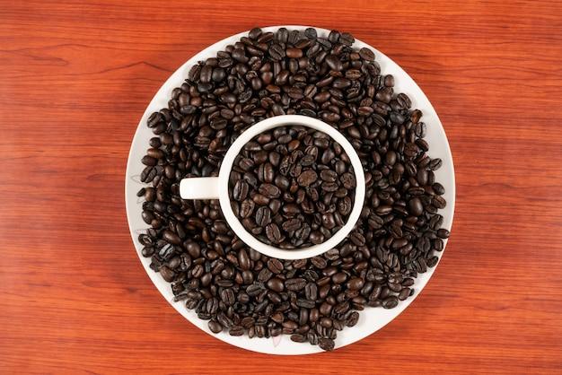 Grains de café dans une tasse blanche avec un fond en bois