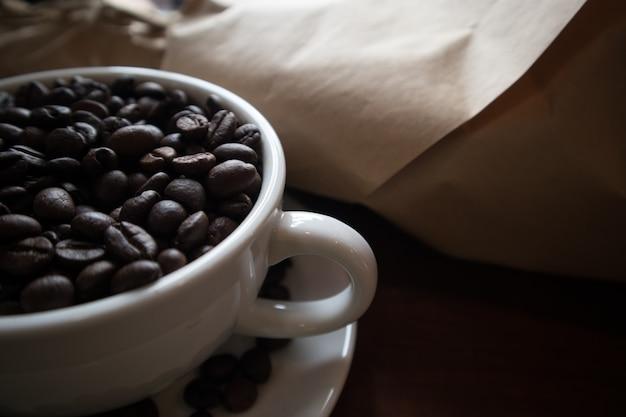 Grains de café dans une tasse à café blanche posée sur une table en bois.
