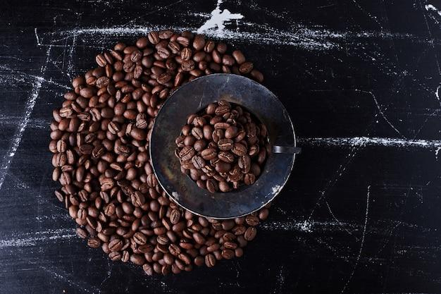 Grains de café dans la tasse et sur le sol.