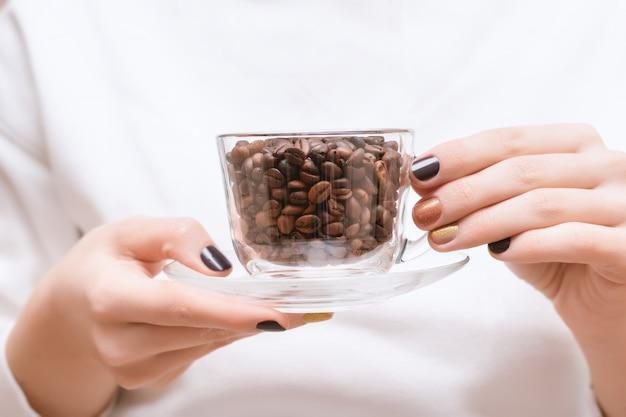 Grains de café dans une tasse en verre sur des mains féminines.
