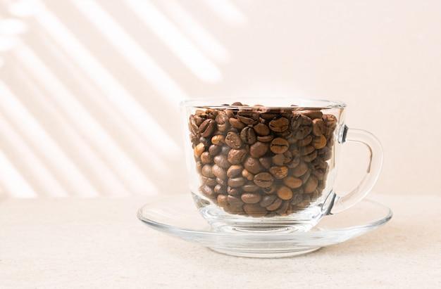 Grains de café dans une tasse en verre sur une table.