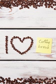 Grains de café disposés dans un coeur et une lettre. autocollant en papier jaune avec mot de pause-café. surface en bois blanc.