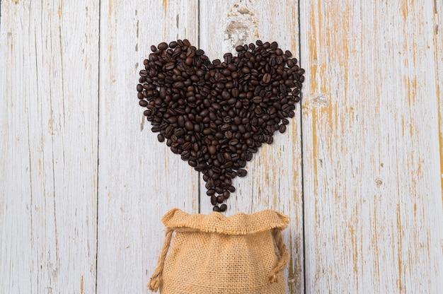 Grains de café disposés en forme de coeur sur fond de bois clair
