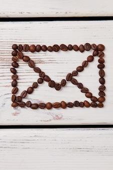 Grains de café disposés en forme de symbole d'enveloppe. surface de planches de bois blanc.