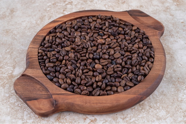 Grains de café empilés sur un plateau en bois