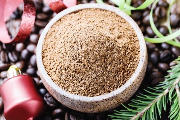 Grains de café entiers et moulus avec des décorations de noël.