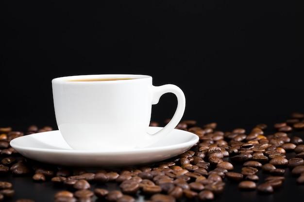 Grains de café entiers et savoureux dispersés dans un ordre chaotique, torréfiés et prêts à l'emploi pour faire des grains de café