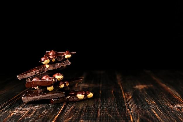 Grains de café épars et chocolat noir sur une table en bois.