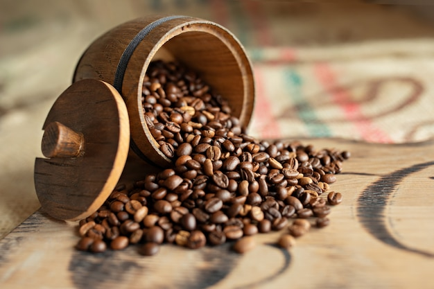Grains de café épars sur une planche de bois. fermer