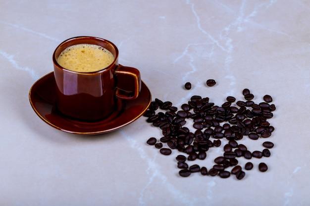 Grains de café épars et tasse à café expresso sur fond de marbre