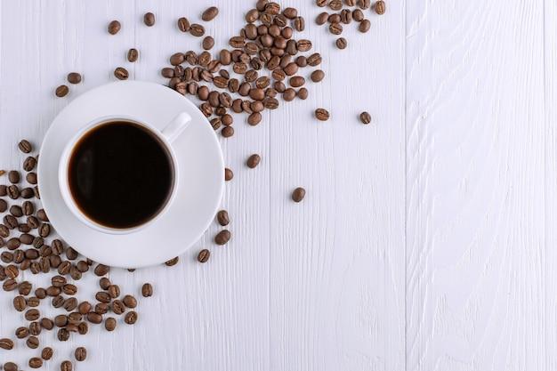 Grains de café épars, une tasse et du chocolat noir sur une table en bois blanche. espace de copie.