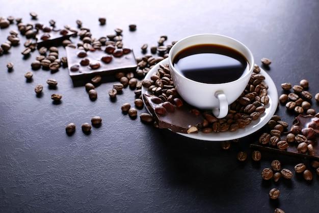 Grains de café épars, une tasse et du chocolat noir sur une table en pierre noire. espace de copie.