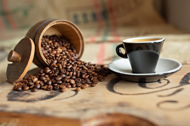 Grains de café épars, une tasse d'espresso, des morceaux de chocolat avec des noix sur une planche de bois.