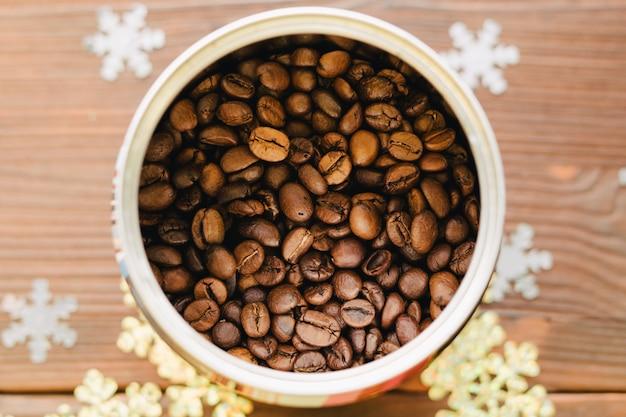 Grains de café en étain sur une table en bois avec des décorations