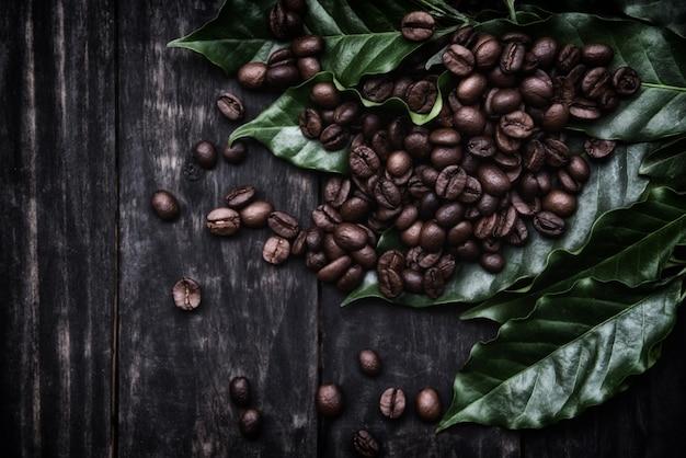 Grains de café sur feuille / café torréfié sur bois foncé
