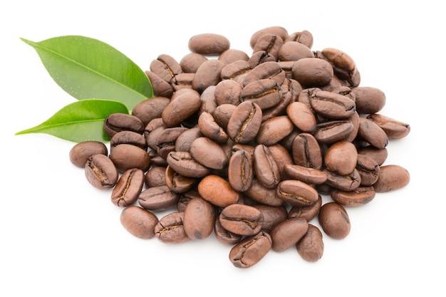 Grains de café et feuilles isolés sur fond blanc.