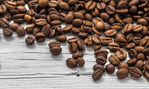 Grains de café sur fond de bois blanc, gros plan