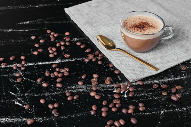 Grains de café sur fond noir avec boisson.