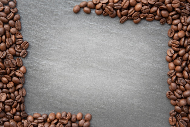 Grains de café sur fond sombre avec la place pour l'espace de copie de texte