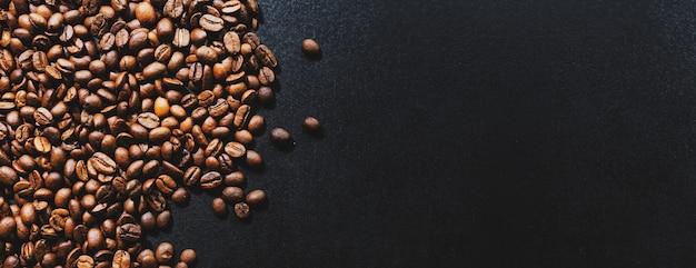 Grains de café sur fond sombre. vue de dessus. notion de café. bannière.