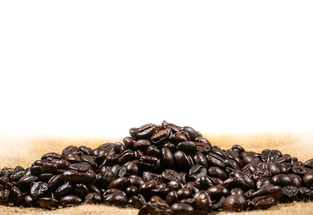 Grains de café sur fond de tissu de lin marron. texture de grains de café torréfiés, utilisée comme arrière-plan. mise à plat, vue de dessus, espace copie.